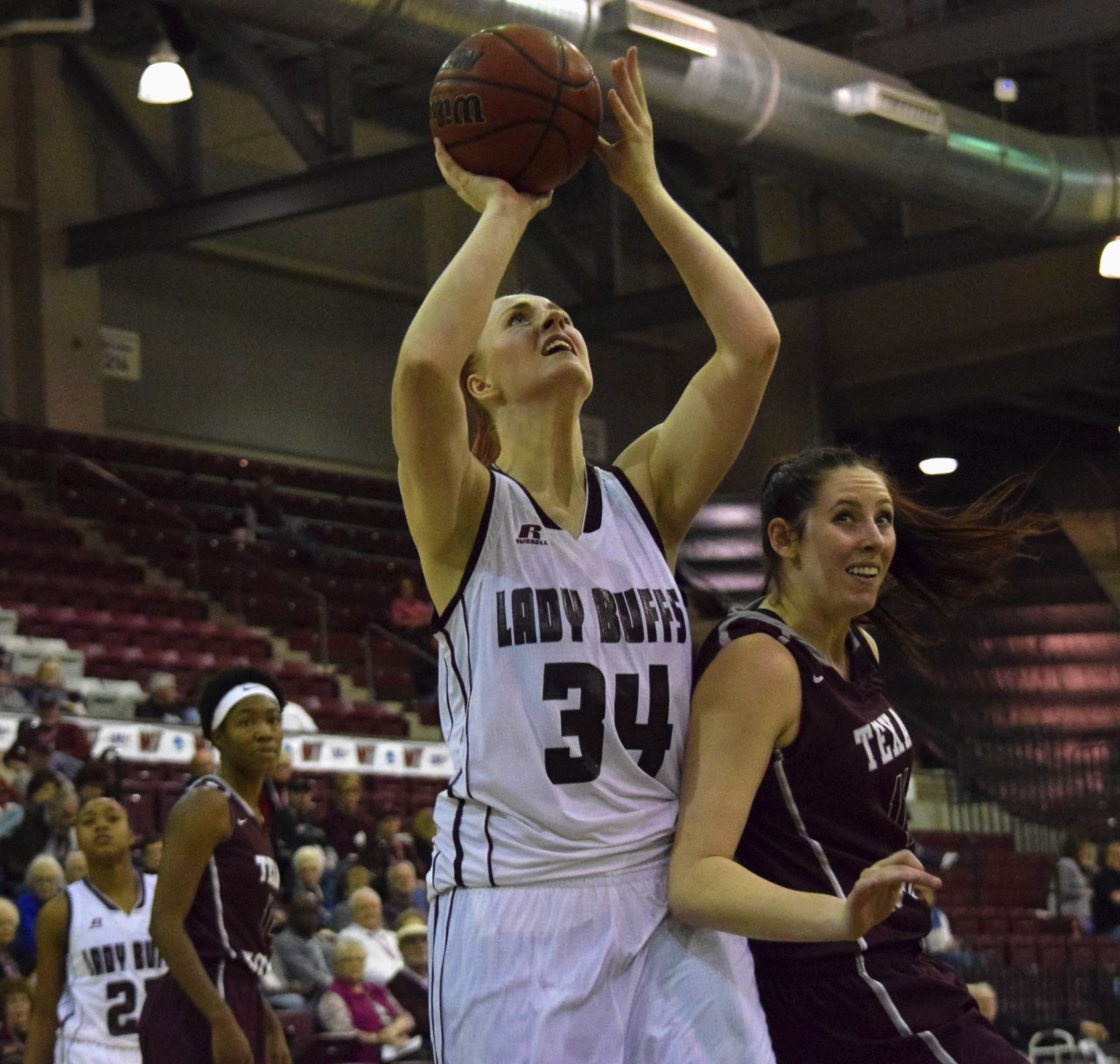 West Texas A&M's Maddison Wild shoots the ball over a Texas Women's University defender during the game on Feb. 4 in the First United Bank Center in Canyon.