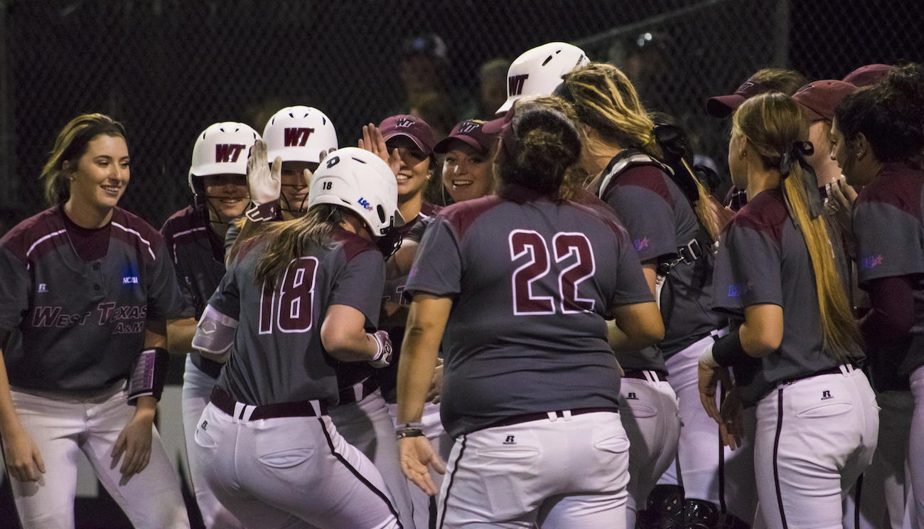 WT's designated hitter Allie Smith (18) comes into home plate with the team celebrating after hitting a home run against Fort Lewis on Feb. 11 at Schaeffer Park.