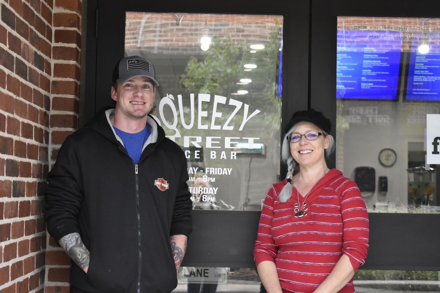 Owners Julie Simmons and Cody Hudson standing in front of the Squeezy Street Juice Bar on the Canyon Square.