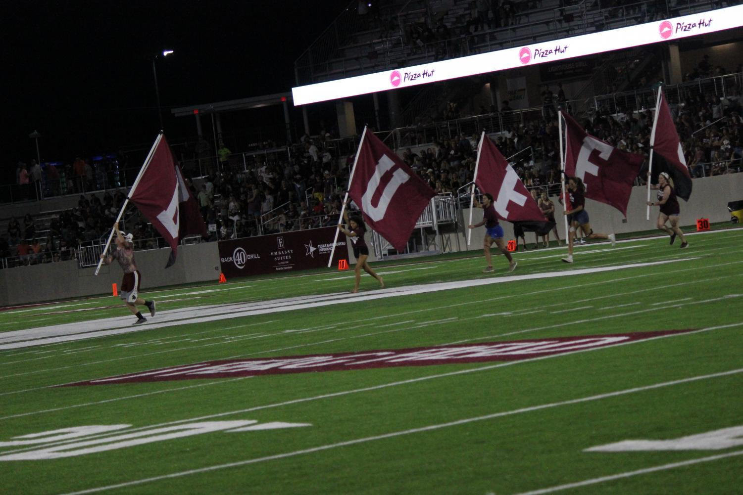 Students+running+with+flags+on+the+field+at+Buff+Stadium+in+celebration+