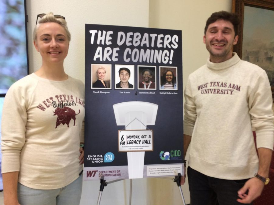 The U.K. Debaters standing by their poster in the Fine Arts Complex.