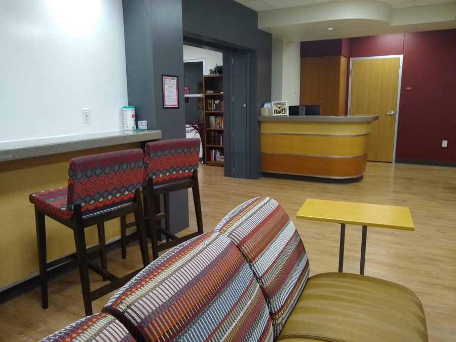 The Multicultural Center's lounge has multiple chairs, a TV and a bar with a whiteboard for artwork or mathematical equations, Thursday, Dec. 4, 2019.