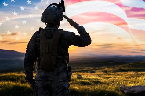 Photo of a military man saluting an image of the American flag in the sky