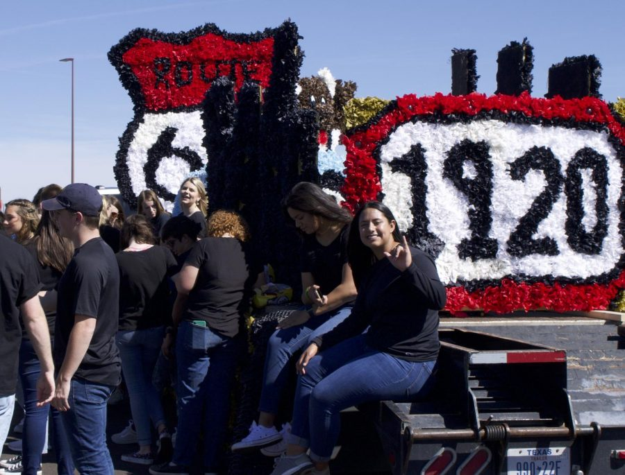 SAGE member,Emily Morgan, throws up the Go Buffs hand sign while SAGE members congregate around their 2021 WTAMU Homecoming parade float waiting for the parade to begin.
